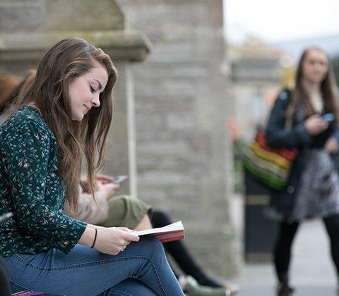 Student studies on campus